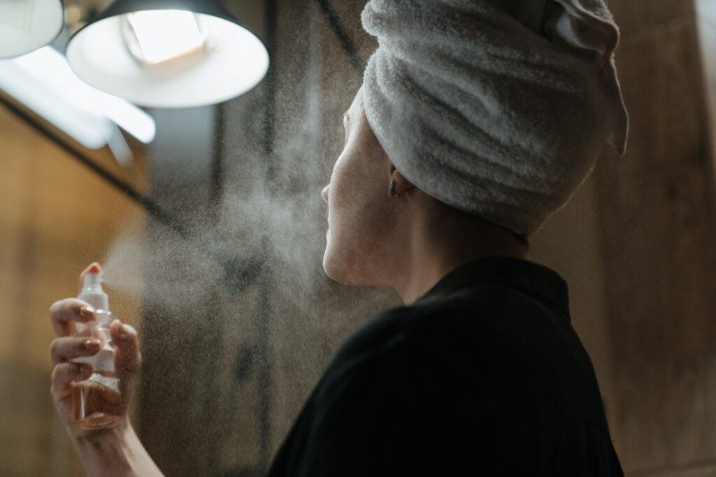 women applying makeup setting spray